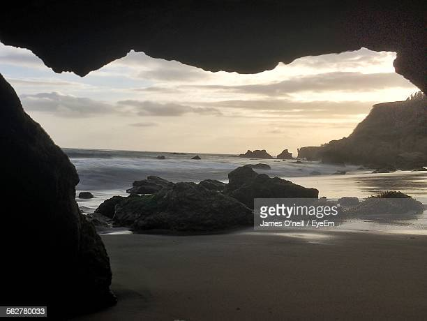 view of beach against cloudy sky - james oneill stock photos and pictures