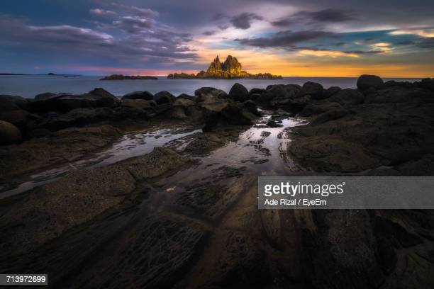 view of beach against cloudy sky - ade rizal stock photos and pictures