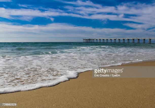 view of beach against cloudy sky - hermosa beach stock pictures, royalty-free photos & images