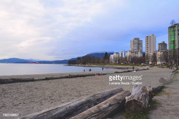 view of beach against cloudy sky - english bay stock photos and pictures