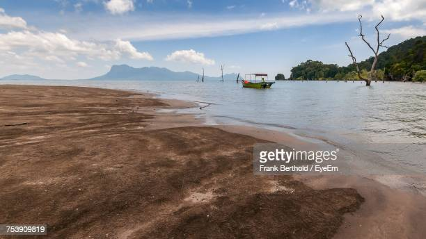 view of beach against cloudy sky - bako national park stock pictures, royalty-free photos & images