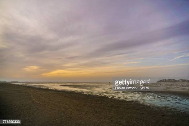 view of beach against cloudy sky - husum stock-fotos und bilder