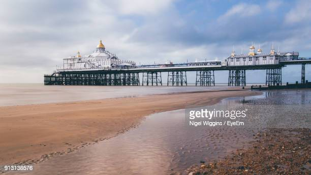 view of beach against cloudy sky - eastbourne stock pictures, royalty-free photos & images