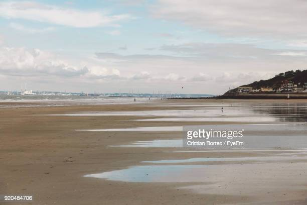 view of beach against cloudy sky - trouville sur mer stock pictures, royalty-free photos & images