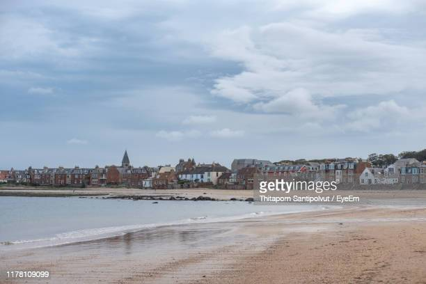 view of beach and buildings against cloudy sky - east stock pictures, royalty-free photos & images
