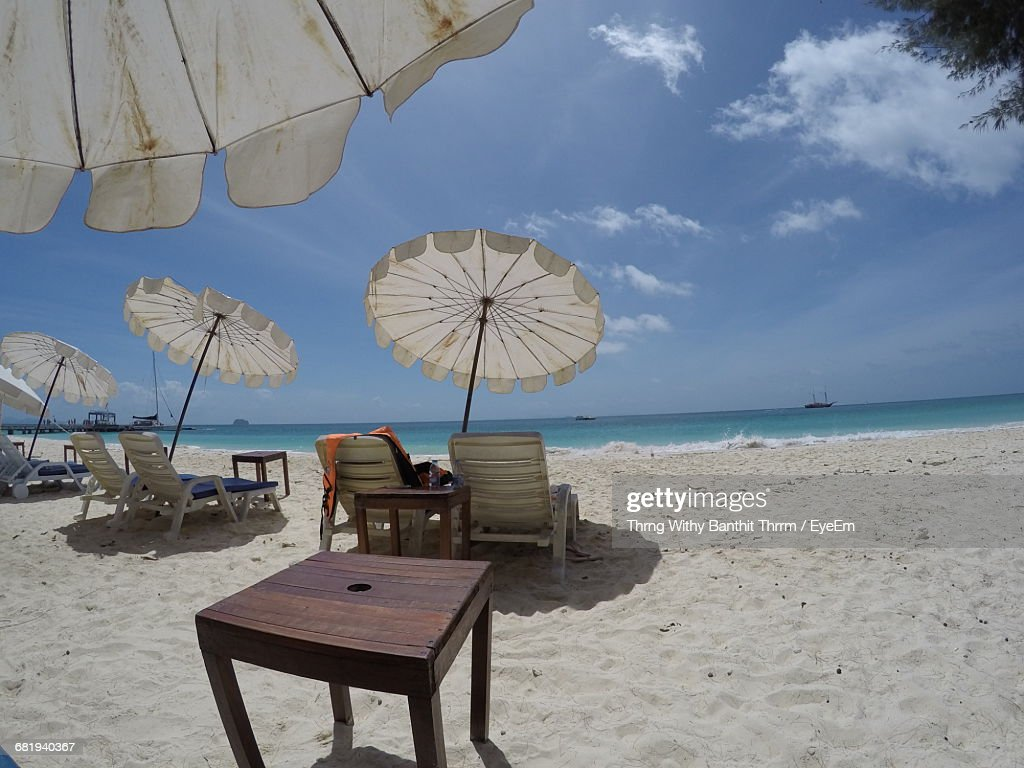 view of beach chairs on white sand and umbrellas against cloudy sky