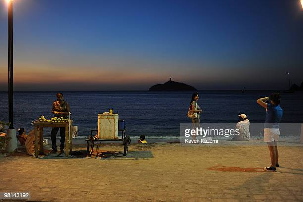 A view of beach front at night with A woman selling soft drinks and fresh fruits by the sidewalk Santa Marta is a city and municipality located in...