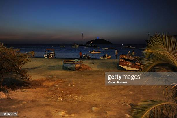A view of beach front at night with fishing boats at shore and boats anchored near the shore Santa Marta is a city and municipality located in...