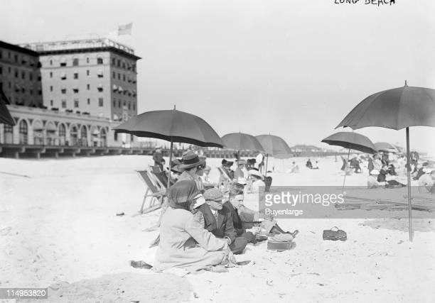 View of beachgoers relaxing under the shade of beach umbrellas at Long Beach in New York early twentieth century