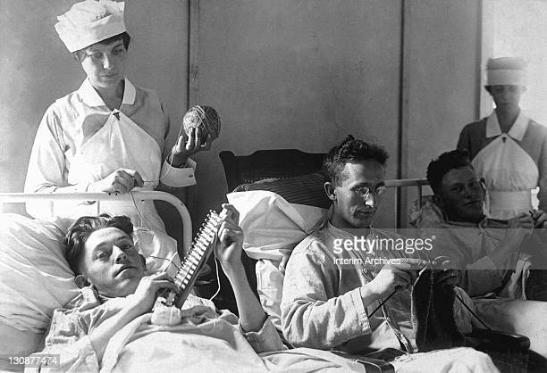 View of bedridden wounded soldiers knitting under the watchful eye of nurses at Walter Reed Hospital in Washington DC 1918