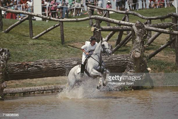 View of Belgian equestrian Karin Dockers riding Britt negotiating a wooden log hazard in to water during competition in the cross country section of...