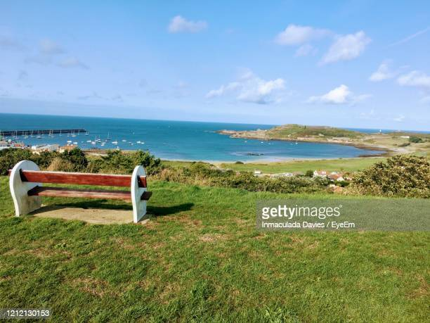 view of bench on beach against sky in alderney - isola di guernsey foto e immagini stock