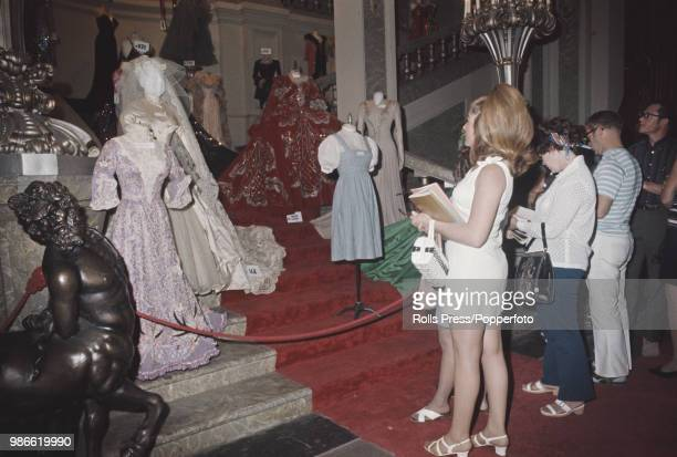 View of bidders observing ornate costume lots on display inside Sound Stage 27 at Metro Goldwyn Mayer Studios during the 1970 MGM auction in Los...