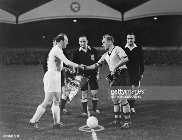 View of Billy Wright the captain of Wolverhampton Wanderers FC shaking hands and exchanging team pennants with Berni Klodt captain of FC Schalke 04...