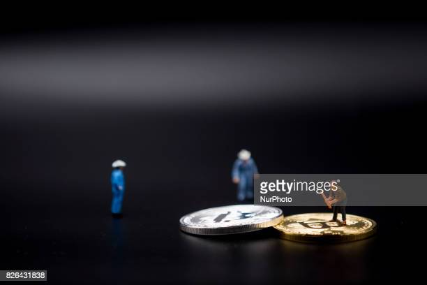 A view of Bitcoin token and a miner miniature figures Bitcoin is a cryptocurrency and a digital payment system invented by an unknown programmer or a...