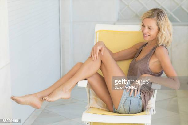view of blonde woman siiting in chair with beauty legs. - leg stock pictures, royalty-free photos & images