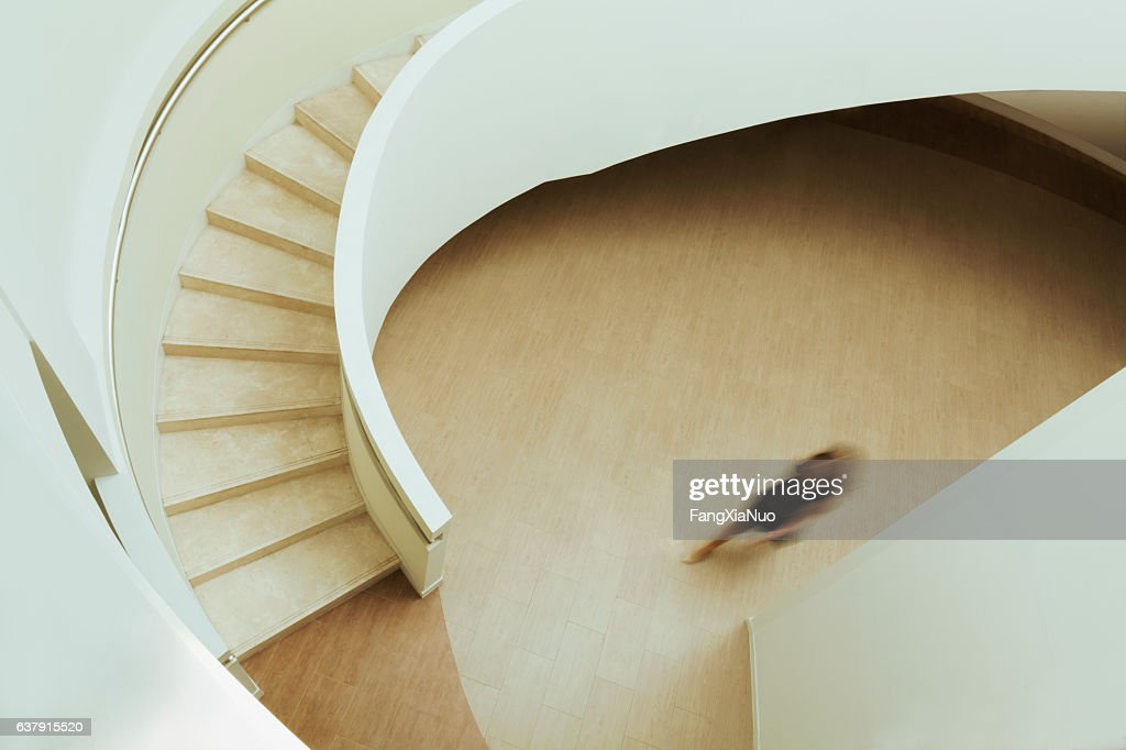 View of blurred person walking towards staircase in building : Stock Photo