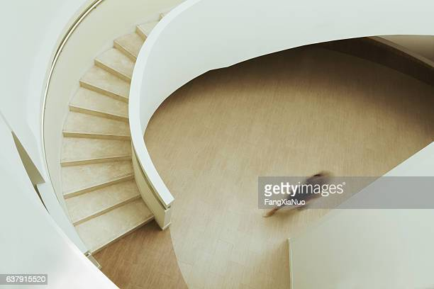 View of blurred person walking towards staircase in building