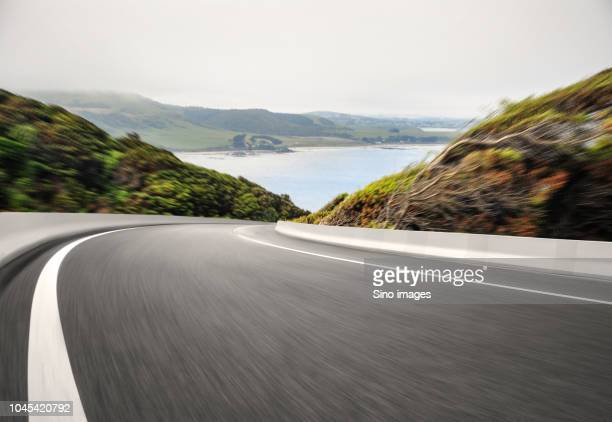 view of blurred road down hillside and lake at foot of hills, new zealand - image stock pictures, royalty-free photos & images