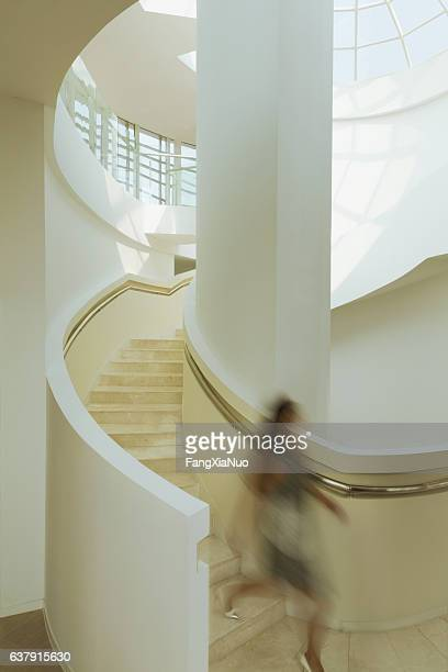 View of blurred woman on staircase in modern building atrium