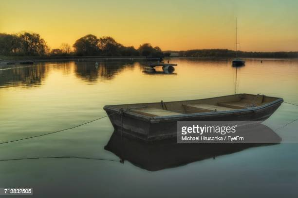 view of boat on calm lake at sunset - michael hruschka stock pictures, royalty-free photos & images