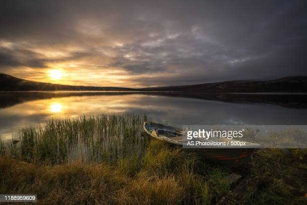 view of boat on lakeshore, dovre, norway - as stock pictures, royalty-free photos & images