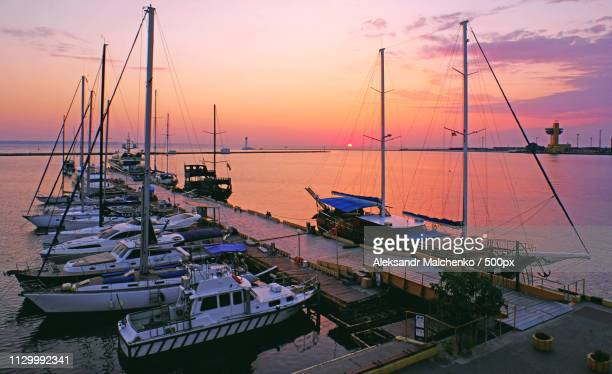 View of boats at harbor during sunrise