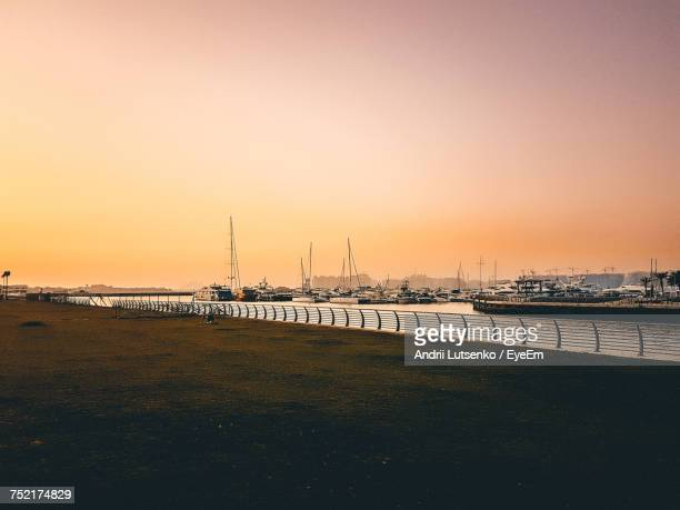 View Of Boats In Harbor At Sunset