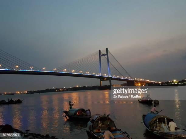 View Of Boats In Hooghly River Against Bridge At Night