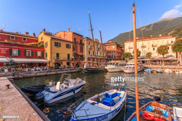 view of boats in malcesine harbour by the lake, malcesine, lake garda, veneto, italian lakes, italy, europe - malcesine stock pictures, royalty-free photos & images