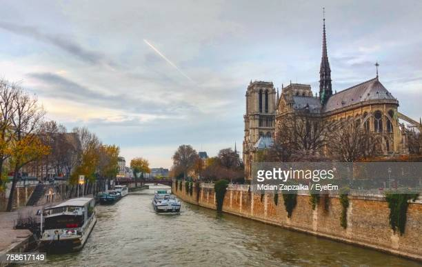 view of boats in river against cloudy sky - spire stock photos and pictures