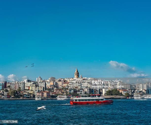 view of boats in sea against buildings - istanbul stock pictures, royalty-free photos & images