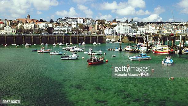 view of boats moored in sea against buildings - isola di guernsey foto e immagini stock