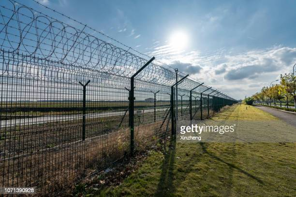 view of border separated by barbed wire against clear sky - prison escape stock pictures, royalty-free photos & images