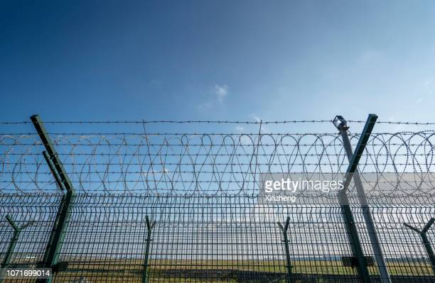 view of border separated by barbed wire against clear sky - refugee camp stock pictures, royalty-free photos & images
