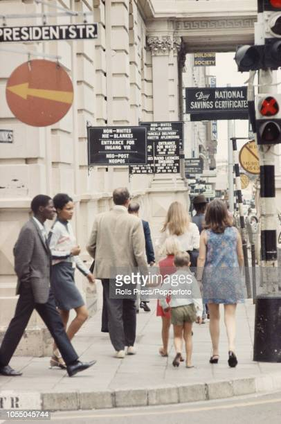 View of both black and white residents walking on a pavement past the entrance to a post office in the centre of Johannesburg during the Apartheid...