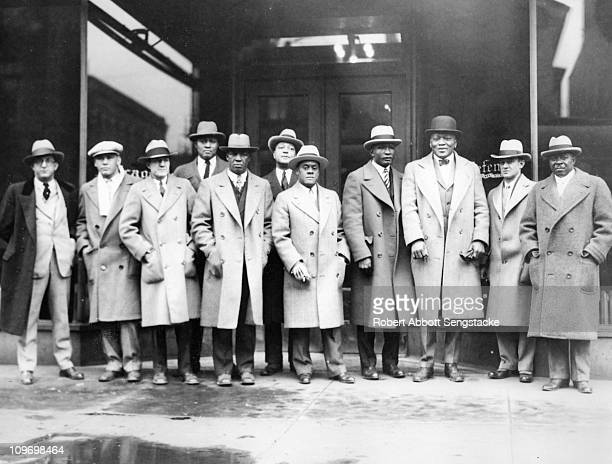 View of boxing champion Jack Johnson third from right standing with a group of men outside the Chicago Defender newspaper offices on 3435 South...