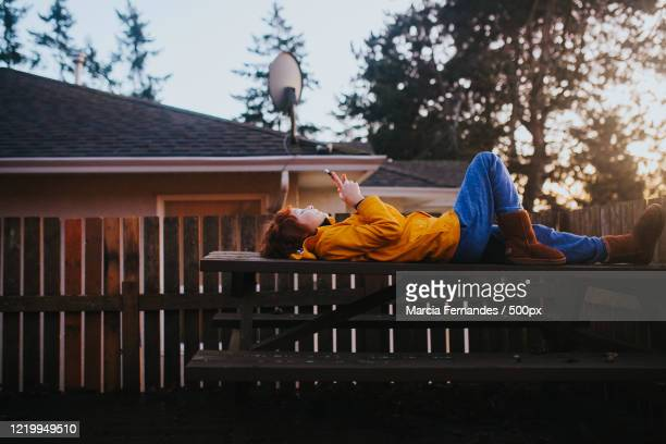 view of boy in his backyard with smartphone - victoria canada stock pictures, royalty-free photos & images