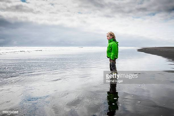 View of boy (4-5) on black arctic beach, Iceland