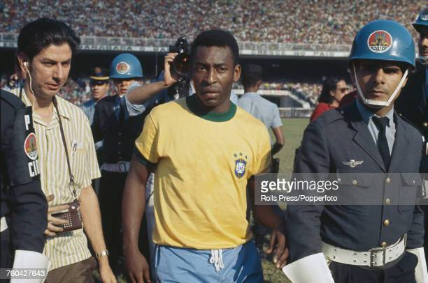 View of Brazilian footballer Pele being escorted on the pitch prior to the Brazil national team's international friendly match with Yugoslavia at the...