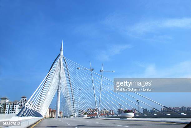 view of bridge against cloudy sky - putrajaya stock photos and pictures