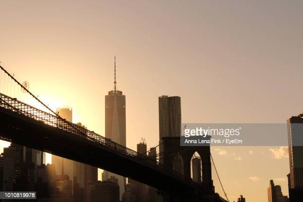 View Of Bridge And Buildings Against Sky During Sunset