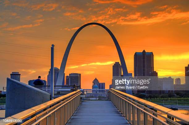 view of bridge and buildings against sky during sunset - ゲートウェイアーチ ストックフォトと画像