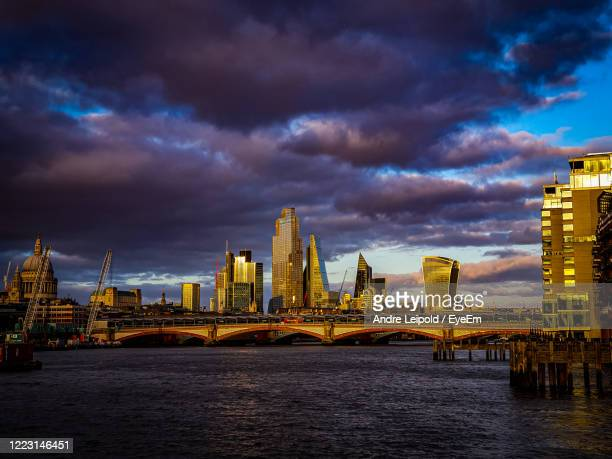 view of bridge over river and buildings against cloudy sky - premiere stock pictures, royalty-free photos & images