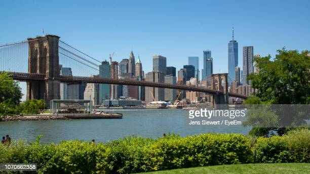 view of bridge over river with buildings in background - jens siewert stock-fotos und bilder