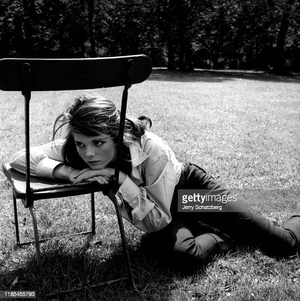 View of British actress Samantha Eggar as she sits on the grass and leans on a chair in Hyde Park London England 1958