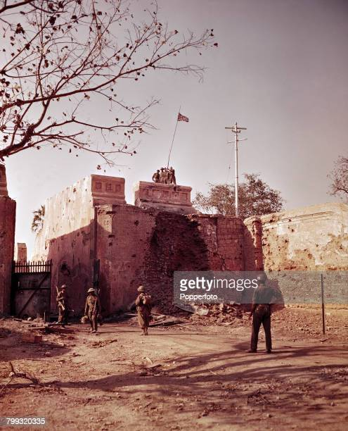 View of British and Allied troops hoisting the union flag over the bomb damaged walls of Fort Dufferin the Mandalay Palace in Mandalay Burma now...