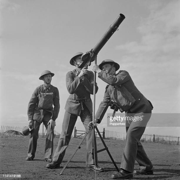 View of British Army soldiers aiming a Lewis Gun at potential enemy aircraft during an anti aircraft training drill at Royal Air Force station RAF...