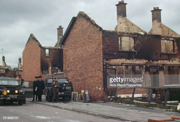 View of British Army soldiers and members of the Royal Ulster Constabulary pictured standing next to burnt out houses in the predominantly Catholic...