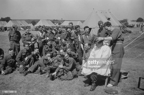 View of British Army soldiers from the British Expeditionary Force pictured watching a fellow soldier having his hair cut as they prepare to return...